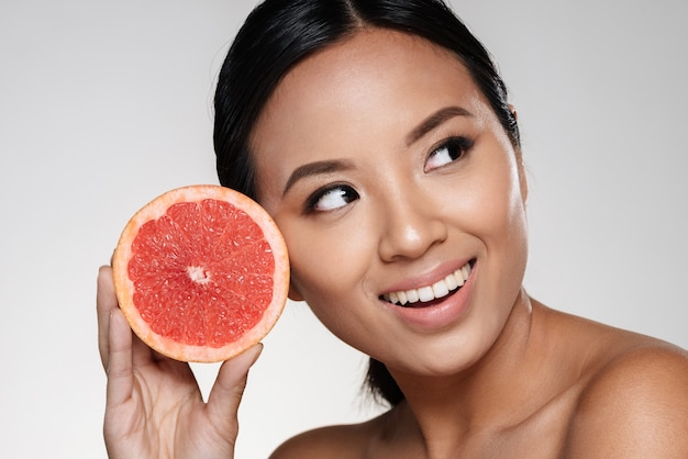 Beautiful asian lady looking aside and holding grapefruit slice near face