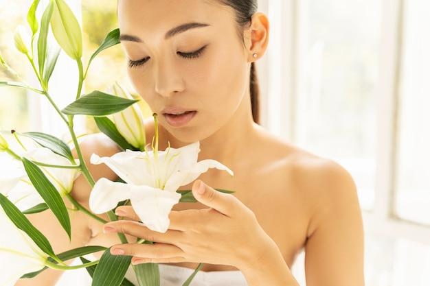 방에 꽃과 함께 아름 다운 아시아 여자
