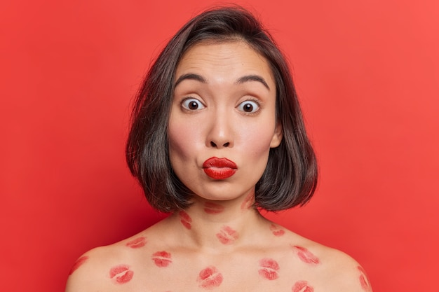 赤い唇を持つ美しいアジアの女性は、明るく鮮やかな赤い壁に対して裸の肩をポーズし、屋内での体のポーズにキスの痕跡を驚かせました