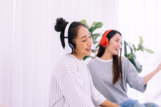 Beautiful asian lesbian couple listening to music together at home,lgbt concept