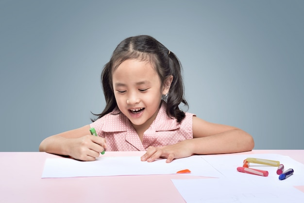 Beautiful asian little girl drawing with wax crayons