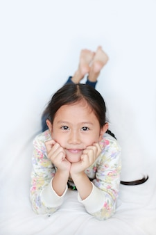 Beautiful asian little girl relaxing with smiling on white bed with looking camera