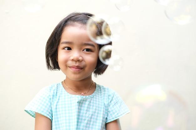 Красивая азиатская маленькая девочка улыбается, глядя на летающие пузыри