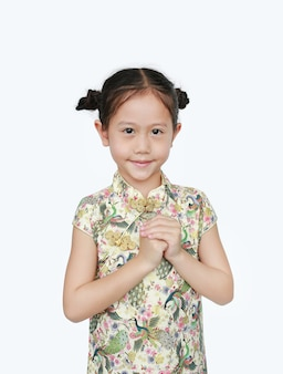 Beautiful asian little girl wearing cheongsam with smiling and welcome gesture celebrating for happy chinese new year isolated