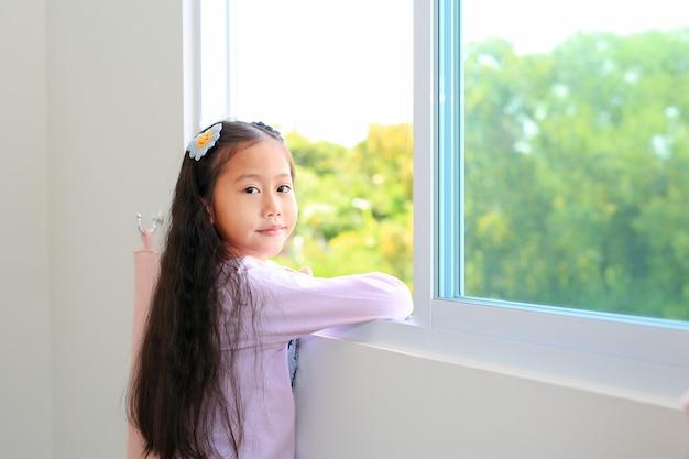 아름 다운 아시아 작은 아이 소녀 집에서 집의 창에 누워.