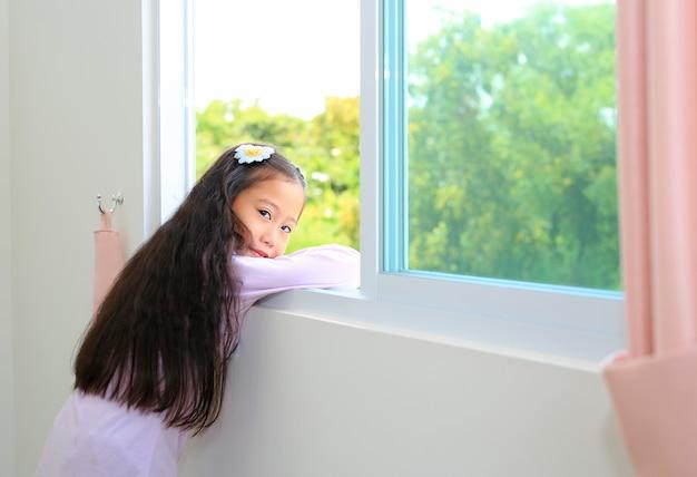 家の窓に横たわっている自宅で美しいアジアの小さな子供の女の子