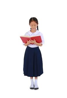 태국 교복을 입은 아름다운 아시아 여학생이 흰색으로 격리된 책을 읽고 있다