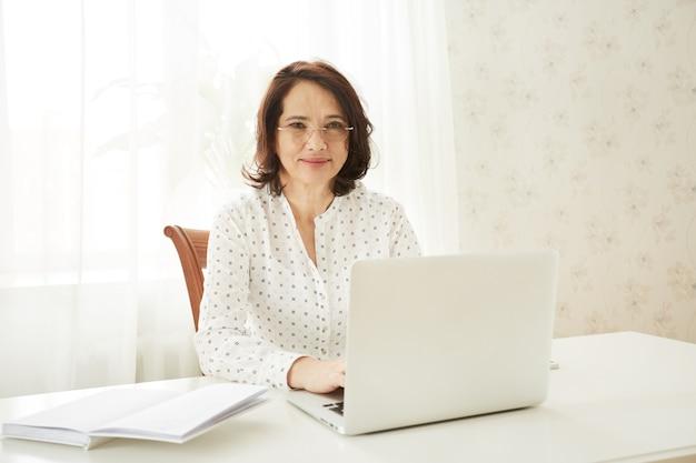 Красивая азиатская зрелая женщина, использующая портативный портативный компьютер