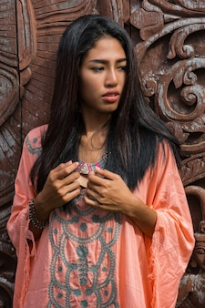 Bello modello asiatico in vestito rosa boho che posa sopra la parete ornamentale di legno.