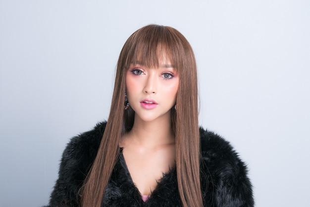 毛皮のコートでポーズ美しいアジアのモデルは、スタジオの照明撮影でのファッション写真です。