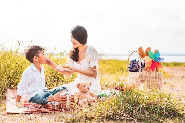 Beautiful asian mom feeding snack to her son in meadow when doing picnic.