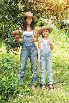 Rambutan 농업 과일 정원에서 아름 다운 아시아 어머니와 딸. 휴일 사람들은 자연 개념을 여행.