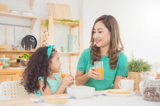 아침에 집에서 함께 아침을 먹고 아름다운 아시아 어머니와 딸