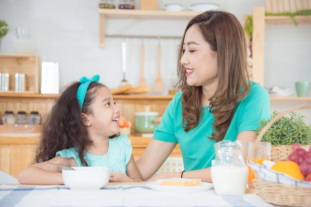 Beautiful asian mother and daughter having breakfast together at home in the morning