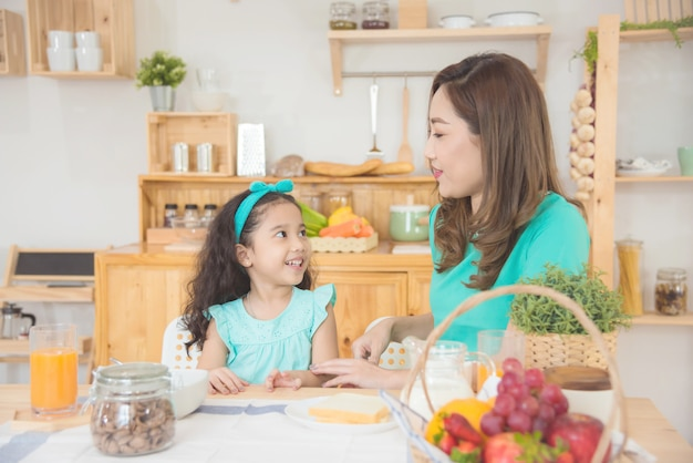 Beautiful asian mother and daughter sitting at breakfast table together at home in the morning