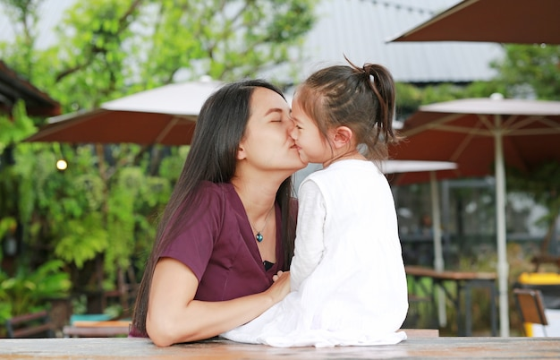 Beautiful asian mother kissing her daughter with love on the wood table at outdoor cafe.