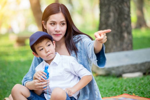 Beautiful asian mother playing with her lovely son hand pointing to looking future concept.