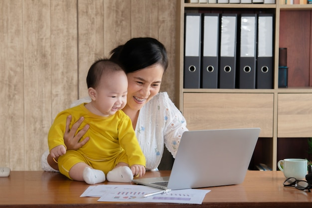 Beautiful asian mother spent time with curiosity toddler baby boy talking, playing on workplace home, adorable naughty son happy laughing with mom hold in hand, single mom feeding multi task working