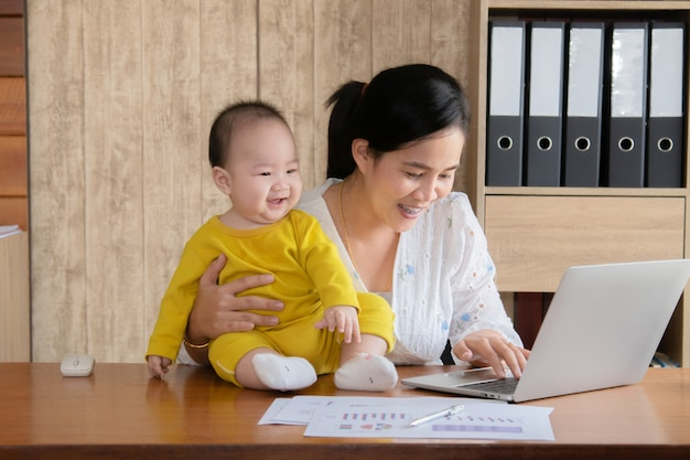 Beautiful asian mother spent time with toddler baby boy talking, playing on workplace, adorable naughty son happy laughing on laptop mom hold in hand, single mom feeding multi task working at home