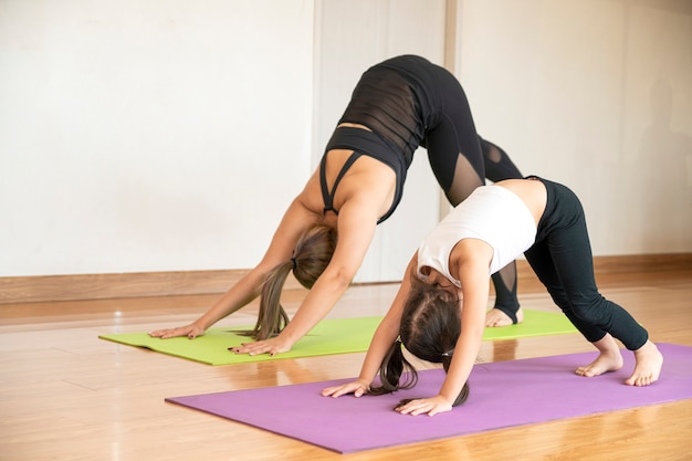 Beautiful asian mother with her daughter doing yoga together at sweet home in relaxing day, happy asian family concept