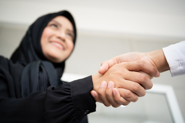 Beautiful asian muslim businesswoman handshake with her colleague close up.