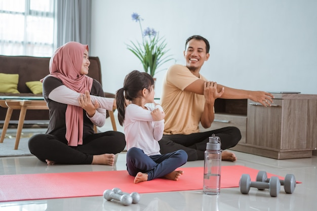 一緒に家で運動する美しいアジアのイスラム教徒の家族。居間でスポーツストレッチをしている親子