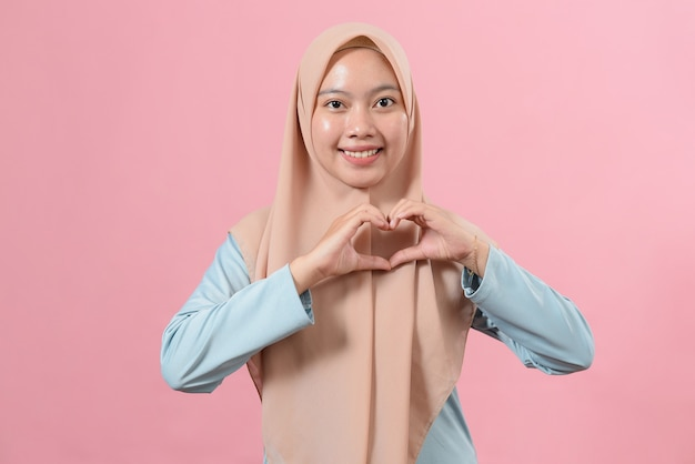 Beautiful asian muslim female makes heart shape gesture, expresses love, says be my love, smiles positively, wears hijab, poses against pink background. body language concept