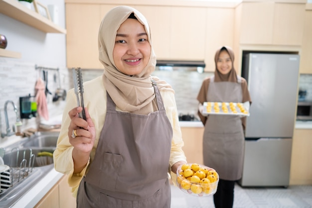 Красивая азиатская мусульманская женщина делает торт настар дома для ид мубарак