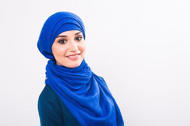 スタジオで白い背景にポーズをとる美しいアジアのイスラム教徒の女性モデル。