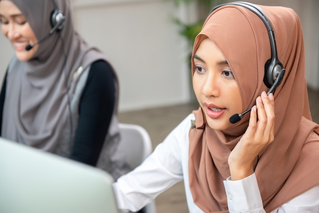Beautiful asian muslim woman working  in call center with team