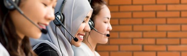 Красивая азиатская мусульманская женщина работая в центре телефонного обслуживания с ее командой