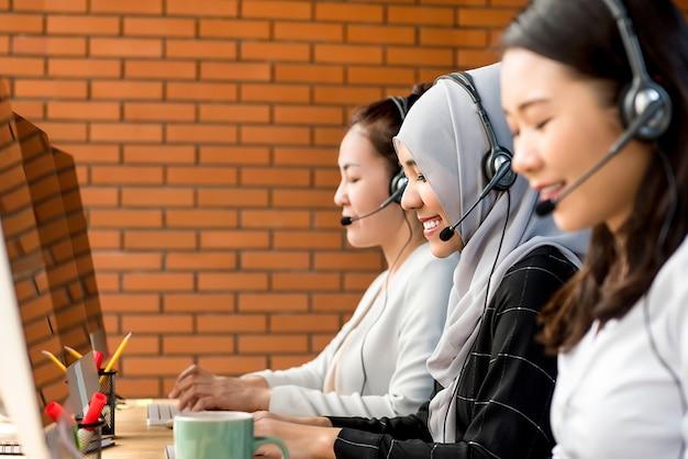 그녀의 팀과 함께 콜 센터에서 일하는 아름다운 아시아 무슬림 여성