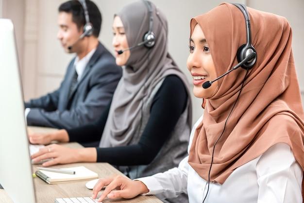 Красивая азиатская мусульманская женщина работая в центре телефонного обслуживания с командой