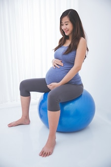 Beautiful asian pregnant woman doing exercise with a swiss ball