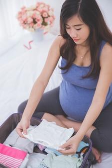 スーツの赤ちゃんの服を整理する美しいアジアの妊娠中の女性