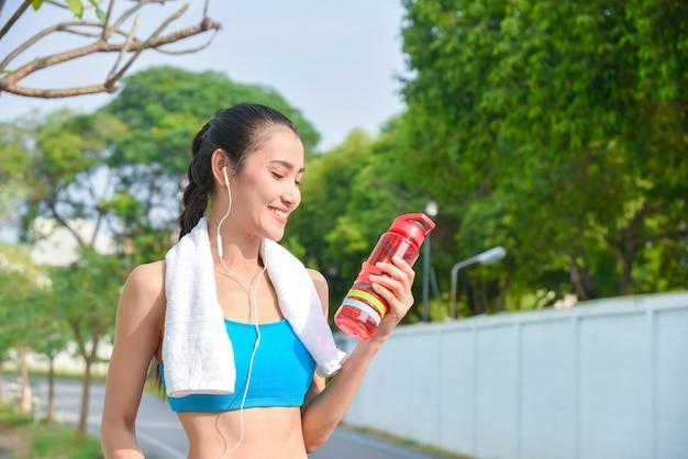 Красивый азиатский бегун держа бутылку с водой и усмехаясь в парке.
