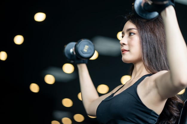 Beautiful asian sexy girl in sportswear lifting the dumbbells in both hand.