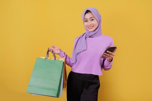 Beautiful asian shopaholic women holding shopping bags, cheerful and joyful using mobile phone