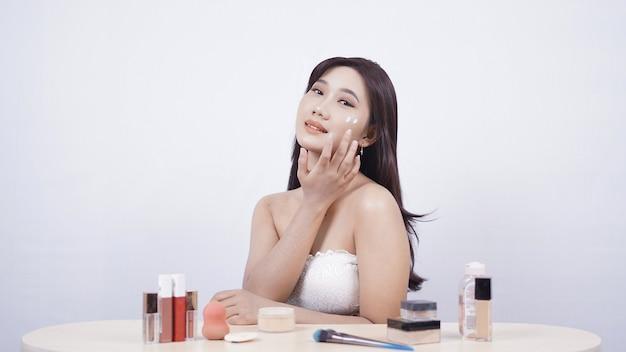 美しいアジアの笑顔は、白い背景で隔離の彼女の頬に顔のクリームを塗ります