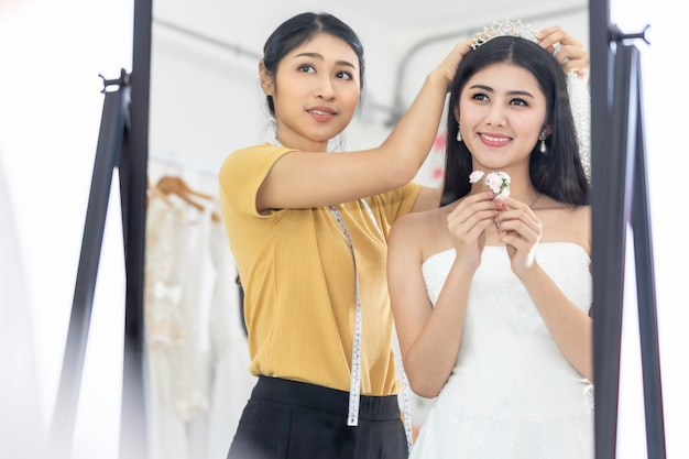 Красивое азиатское усмехаясь и пробуя на платье свадьбы в магазине.