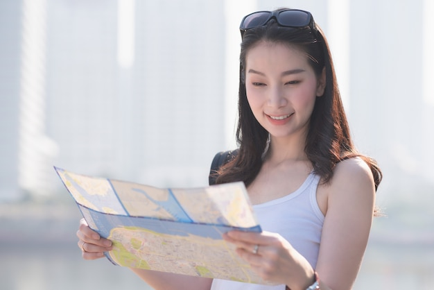 Beautiful asian solo tourist woman  looking at the map searching for tourists sightseeing spot.