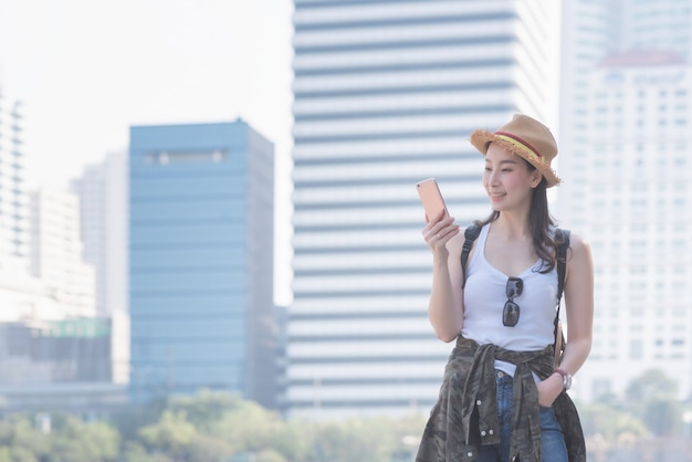 Beautiful asian solo tourist woman smiling and looking at mobile phone
