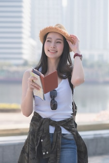 Beautiful asian solo tourist woman  smiling and searching for tourists sightseeing spot.