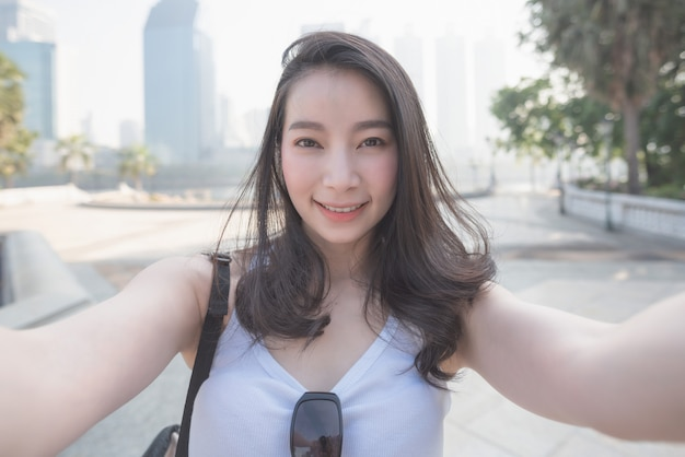 Beautiful asian solo tourist woman taking selfies on a camera in urban city downtown