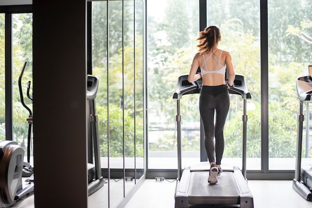 Beautiful asian sport woman is running on treadmill in the gym