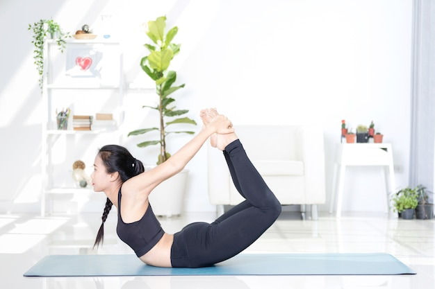 Beautiful asian sports woman performs the exercises at home .yoga