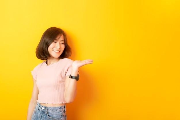 Красивый азиатский студент счастливый на желтой стене