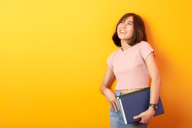 Beautiful asian student happy on yellow wall