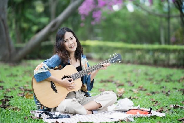 Красивый азиатский студенческий пикник в парке и размышления о сочинении песни