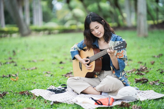 Beautiful asian student picnic in the park and thinking composing song